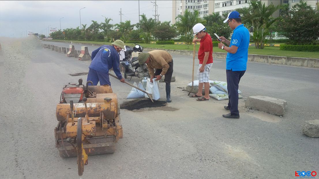 Nhân công dùng xẻng san phẳng bê tông trước khi lu